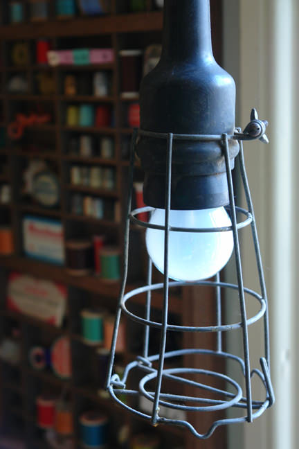 view of our craft & sewing room showing a vintage hanging industrial lamp