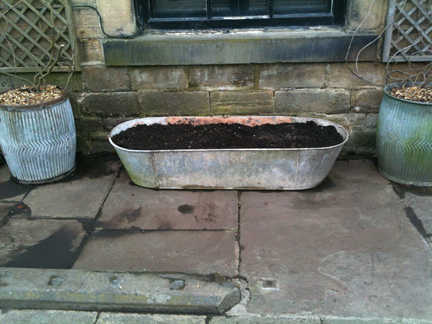 pair of galvanised dolly tubs and large tin bath prepared for planting
