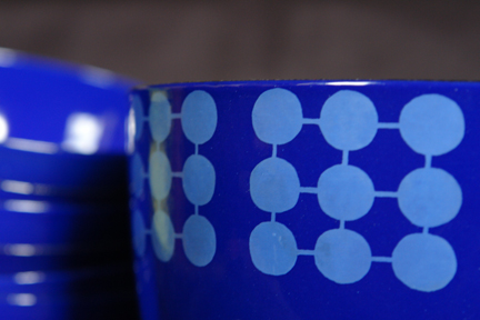 detailed view of a collection of blue vintage Finel enamel bowl decorated with circles in a square pattern