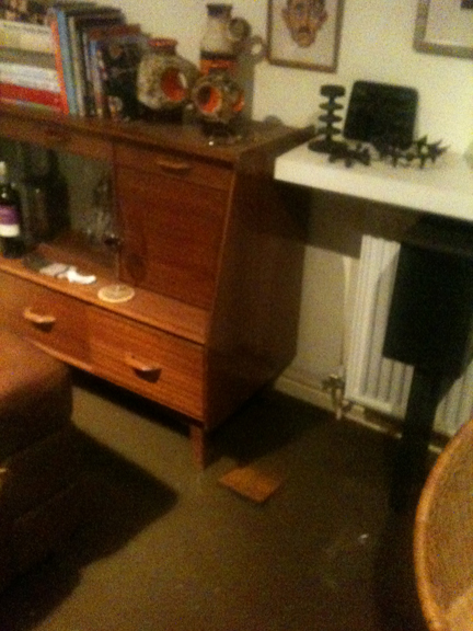 A 1950s G Plan sideboard in our sitting room with flood water surrounding it