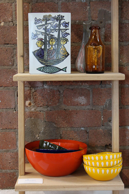 shelves with midcentury modern items including vintage Catherineholm enamel bowls and folk art tile