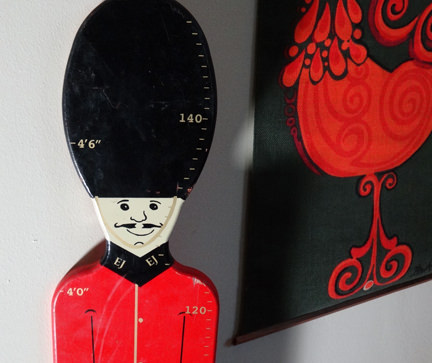 detail from a vintage wooden child height measure in taking the form of a Grenadier Guard