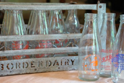 vintage metal milk crate with vintage milk bottles
