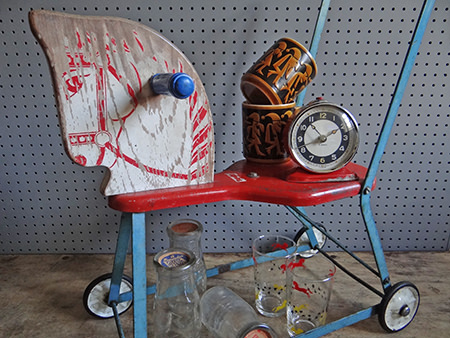 collection of vintage homwares including a vintage push along horse, pair of Hornsea Pottery 7 Dwarfs mugs, Manchester milk bottles and atomic drinking glass set in rack