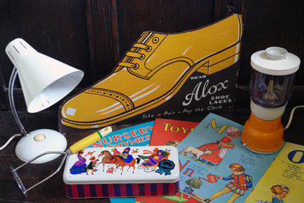 selection of vintage homewares at H is for Home including white goose neck desk lamp, US Advertising sign for Alox shoelaces, trio of 1950s counting & alphabet picture books, orange electric food processor, potato masher and chocolate biscuit tin