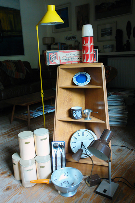 "selection of vintage items to be shortly added to the H is for Home shop including triangular corner shelf unit, desk lamps, bright yellow Habitat floor lamp, 1950s cream coloured storage tins, blue Hornsea ashtray, Hornsea ""May"" mug, red thermos flask, white Metamec wall clock, stainless steel tea strainer, ""Gaybox"" wall fitting, orange-handled aluminium colander and Scandinavian salad servers"