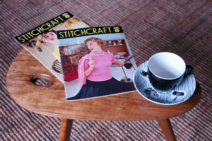 vintage 1950s palette topped teak table with splayed legs with Ridgeway Homemaker tea cup & saucer and two vintage 1950s Stitchcraft magazines