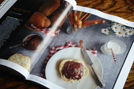 image in a magazine showing bread sticks and slice of bread with chocolate spread on a plate with glass of milk with striped straw