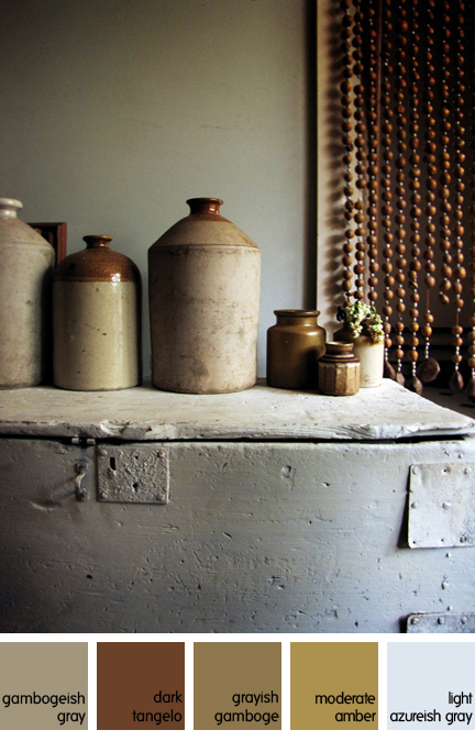 collection of vintage pottery jars on a white painted rustic chest