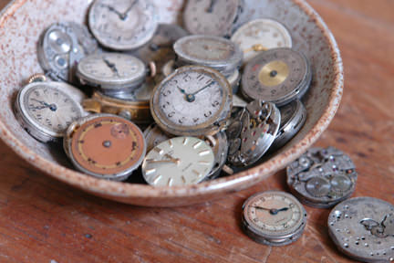 collection of vintage watch faces in a pottery bowl