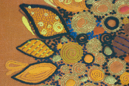 detail from a framed &amp; glazed vintage wool work in shades of orange featuring a sunflower