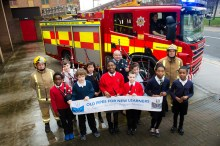 Children and firefighters with the sign in front of the fire engine