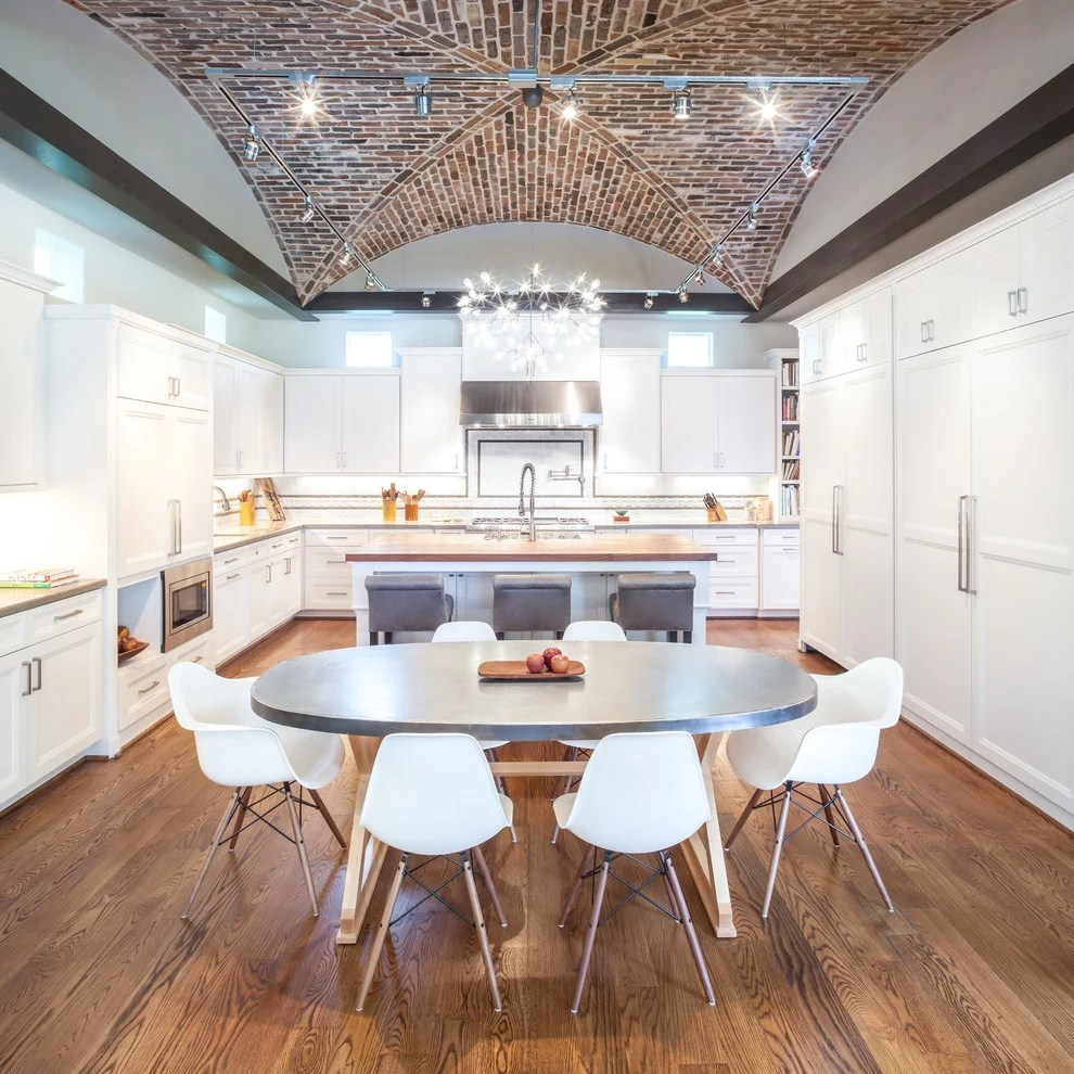 kitchens vaulted ceilings overhead kitchen lighting Winter white wall lined with white cabinets paired with a grey dining table and white