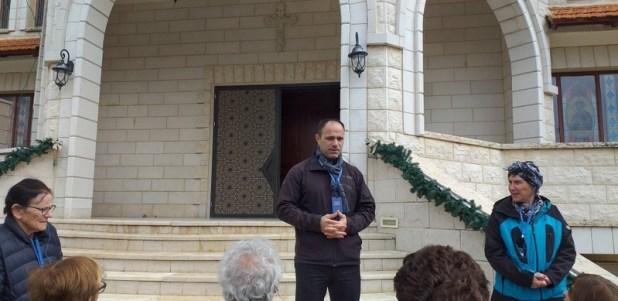 שאדי מרצה בפני מטיילים על מדרגות הכנסייה