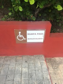 Wheelchair sign in spanish, seemingly translated to 'ramp for less valid'