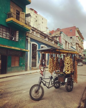tricycle full of hanging garlic on Cuban street