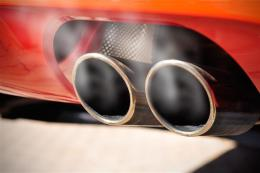 Close up of a red car dual exhaust pipe with smoke around it