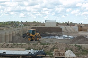A bulldozer moves sand that has been cleaned for reuse into piles for storage.