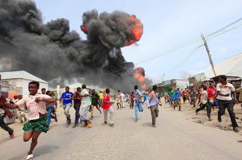 People escape from the direction of a huge fire-ball after an accidental explosion at a petrol storage facility within the former U.S. residential housing in Mogadishu