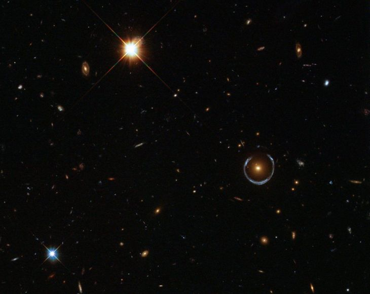 believe-it-or-not-this-is-a-real-hubble-image-and-that-bizarre-blue-ring-toward-the-right-is-an-optical-illusion-produced-when-gravity-bends-light-in-a-phenomenon-called-gravitational-lensing-astronomers-have-used-this-te