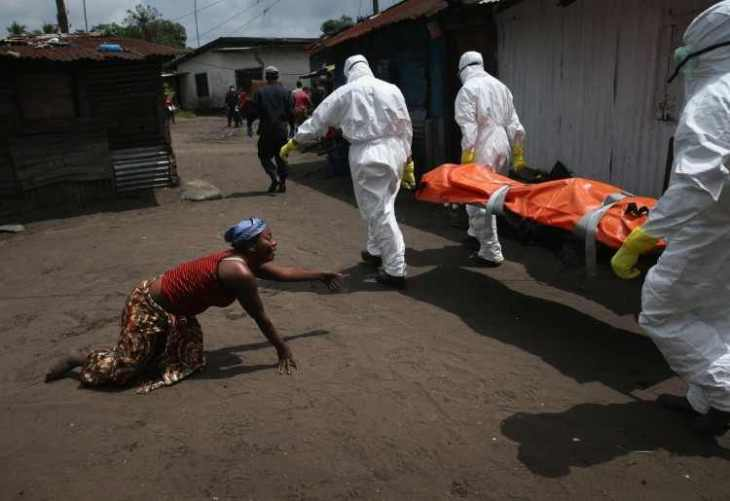 a-woman-crawled-toward-the-body-of-her-sister-as-an-ebola-burial-team-took-her-for-cremation-in-october-the-burial-of-loved-ones-is-important-in-liberian-culture-making-cremation-traumatic-for-surviving-fam-75