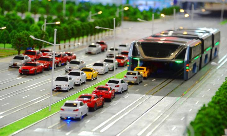 A model of the 'Transit Elevated Bus' is on display during the 19th China Beijing International High-tech Expo (CHITEC) in Beijing, China, 19 May 2016. Getting stuck in a traffic jam can be one of the most frustrating parts of travelling around a busy city. Now engineers in China, the world's most populated country, have come up with a way to overcome the problem of getting around in traffic. Designs for a new elevated bus has been unveiled at a tech expo in China, which will apparently be able to carry 1,200 passengers over the top of cars and let traffic to pass underneath it. The scale model of the 'Transit Elevated Bus' was demonstrated this week at the 19th China Beijing International High-Tech Expo. The idea is that passengers sit far above other vehicles on the road, allowing cars to pass underneath. In a model of the vehicle, it appears to run on a set of fixed rails embedded on the road. It means the vehicle is more like a cross between a tram and a bus. Engineers hope the design will increase the availability of the road space, and cause fewer traffic jams than regular buses. It is also expected to save costs compared to other public transport options, like the subway.