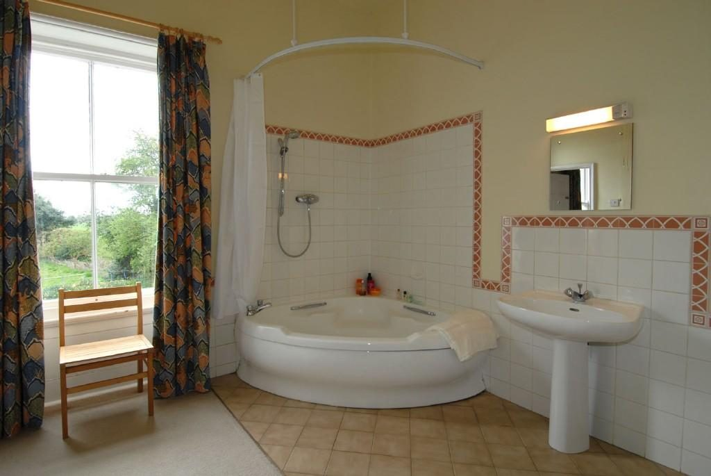 Spacious area using bathroom corner bath ideas with white curtain and