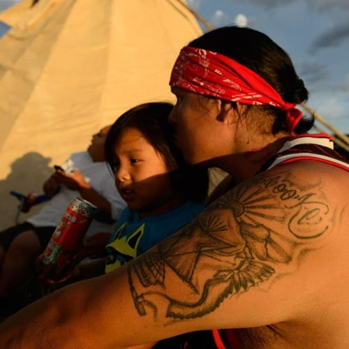 Elijah Laforge holds his son at the Medicine Horse camp near Crow Agency, Montana. The tattoo on his arm reads Apsáalooke, the name of the Crow Nation. @natgeocreative