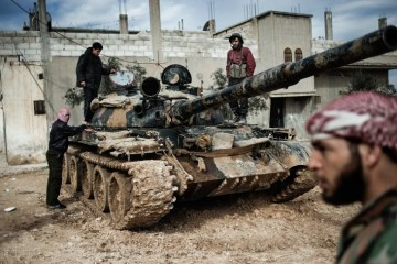 Feb. 23, 2012. A Free Syrian Army member prepares to fight with a tank whose crew defected from government forces in al-Qsair