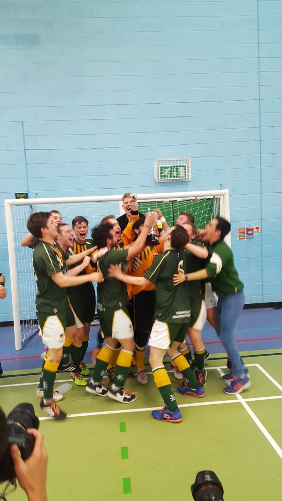 The victorious men's futsal team celebrate their Varsity victory.