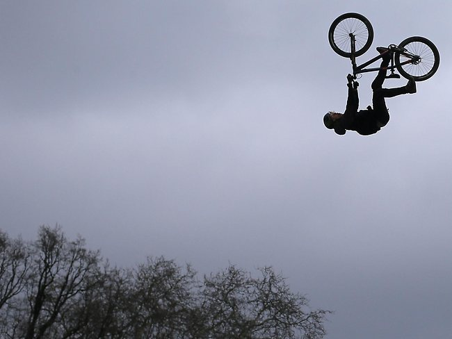 ORIGINAL CAPTION: Canada's Brett Rheeder jumps in the air with his bike as he competes, during the Red Bull Vienna Air King dirt jumping competition held in front of the Rathaus (townhall) in Vienna. Rheeder won the 2013 event which is held every spring in the Austrian capital, and marks the season opening of the Freeride Mountain Bike (FMB) World Tour.