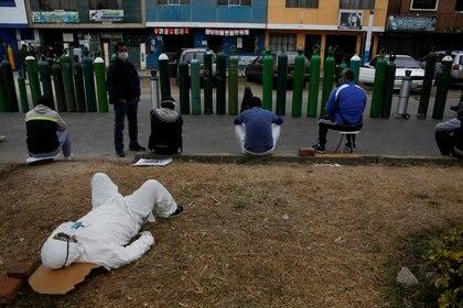 Un hombre con un traje protector descansa mientras la gente espera junto a los tanques de oxígeno fuera de un distribuidor privado que recarga los tanques en Lima, Perú, el 25 de junio de 2020 (REUTERS/Sebastian Castaneda)