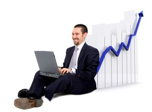 business man on a laptop sitting on the floor with a growth and success chart