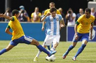 Argentina forward Lionel Messi dribbles between Brazil midfielder Romulo and Sandro during their international friendly soccer match in East Rutherford