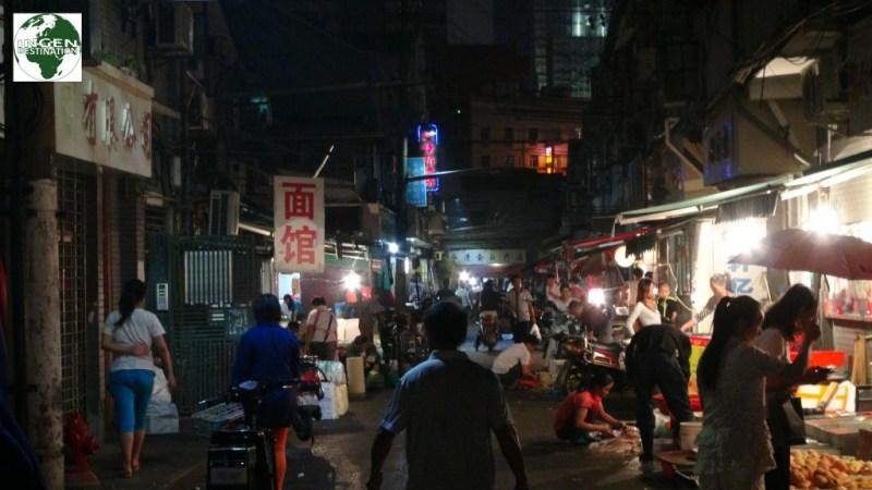 En sidegade til Nanjing - pigen i den røde bluse skærer fisk direkte på asfalten. Sådan var hygiejnen desværre mange steder.