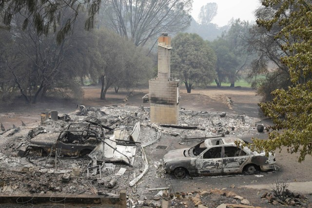 Only a chimney and burned cars remain at a home destroyed by fire Sunday, Sept. 13, 2015, in Hidden Valley, Calif. (AP Photo | Eric Risberg)