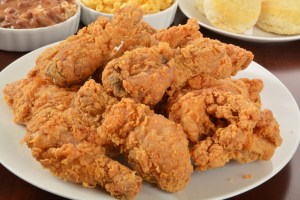 A plate of delicious friend chicken with side dishes in the background.