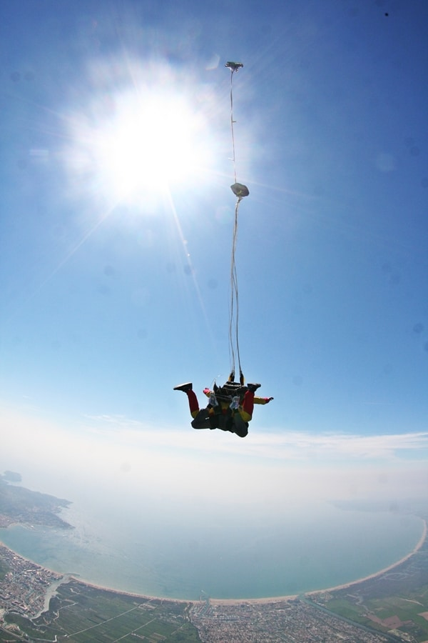 About skydives - tandem fall against blue sky and clouds