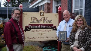 Washington Business Improvement District Executive Director John Monteverde (left), on behalf of the WBID Board of Directors, recognizes DeVoe Funeral Home and Mark and Susan DeVoe with a plaque commemorating their 100 years of family business.