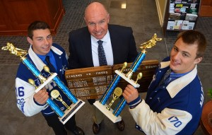 Pictured, left to right, are Warren Hills' Shane Deemer, MVP (Offense), Coach Larry Dubiel (holding a ceremonial Beater Board), and Kurt Nemeth, MVP (Defense). The decorated Beater Board is awarded to the winning team each year and celebrates the county's agricultural heritage.