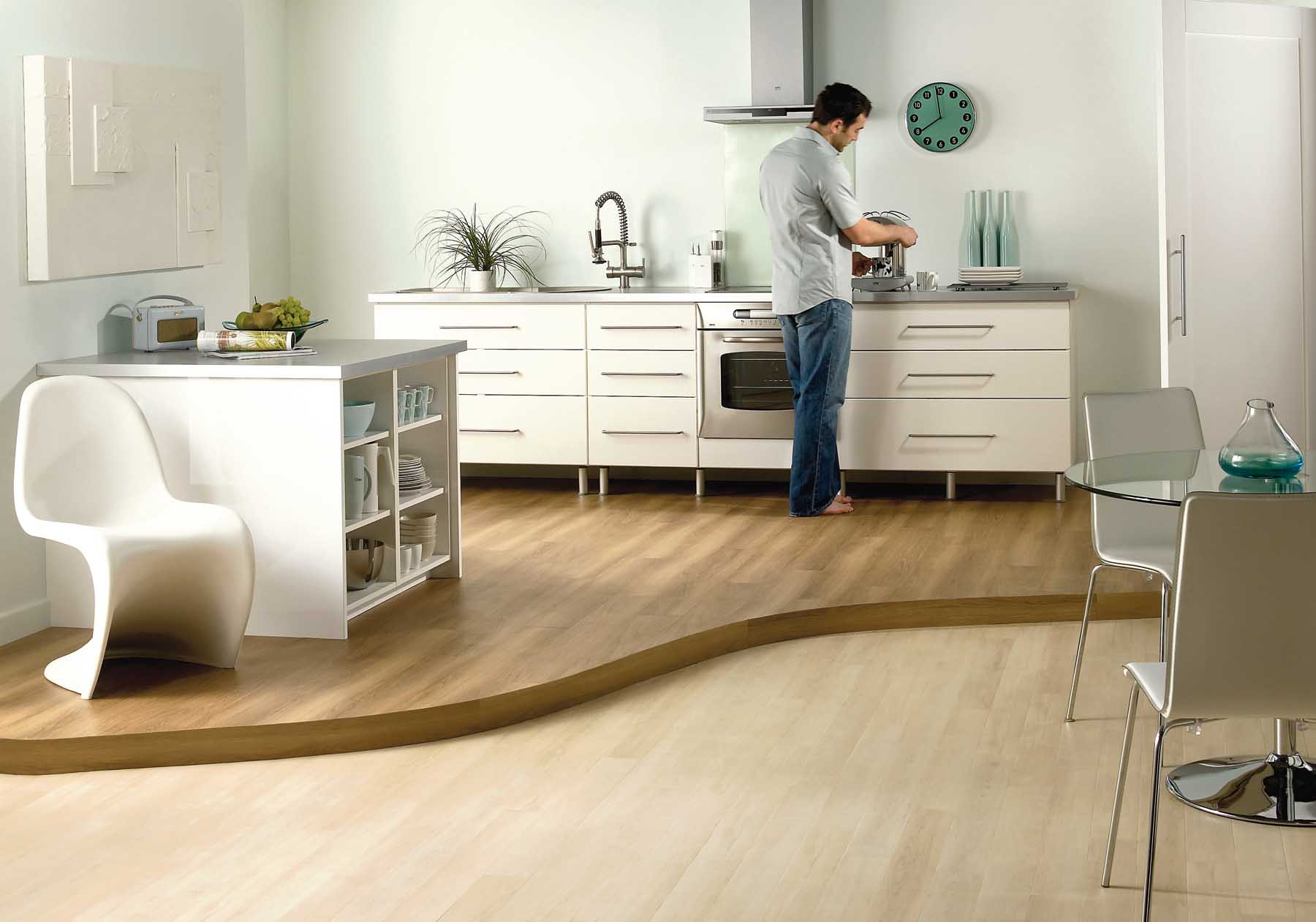 Laminate flooring kitchen delivered by Inspire Flooring Aberdeen where a man is preparing a cup of coffee