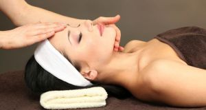 Beautiful young woman in spa salon taking head massage