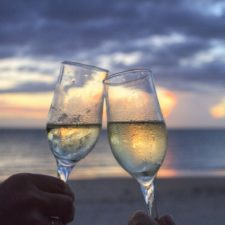 friends toasting the IRS with champagne flute on beach at sunset