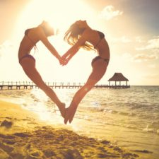 Female friends holding hands and jumping on beach in heart shape at sunset - ESG