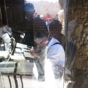 Modern scribe in an airconditioned enclosure in the ancient synagogue