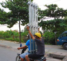 Carrying a metal gate on a scooter in Vietnam