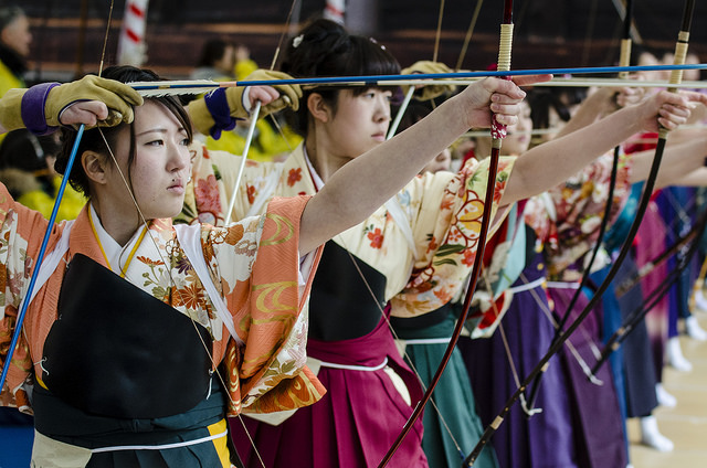 """New Year Archery in Sanjuusangen-dou, Kyoto. Wikipedia: """"the Tōshiya or Festival of the Great Target still continues today, drawing roughly 2,000 participants from throughout Japan. Archers shoot arrows into targets approximately 50 – 100 centimeters in diameter and 60 meters (198 feet) away at the opposite end of the veranda. It is held on the second Sunday of January in conjunction with the temple's most important mass, the Yanagi-no-Okaji, or Rite of the Willow ritual and Japan's Coming of Age Day"""""""