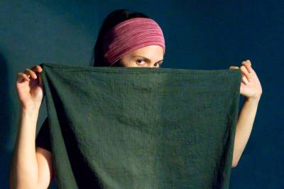 Woman using a piece of fabric as a face cover.