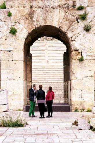 Three people standing in front of an arch entrance to the Odeon of Herodes Atticus, in Athens.