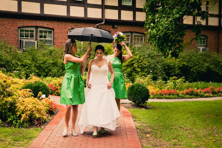 bride with green bridesmaid dresses under umbrella